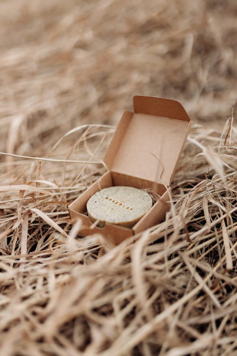 Nokkonenkehakukkashampoopala kauniissa paketissa heinien keskellä.
